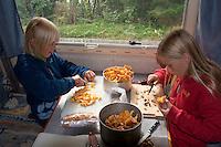 Kind, Kinder putzen und schneiden gesammelte Pfifferlinge am Tisch im Wohnmobil, Outdoor, Pilzernte, Pilz-Ernte, Echter Pfifferling, Eierschwamm, Cantharellus cibarius, chanterelle