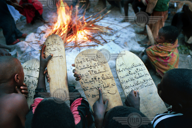 Fulani villagers from the muslim village study the Koran from wooden tablets as they sit beside a fire..