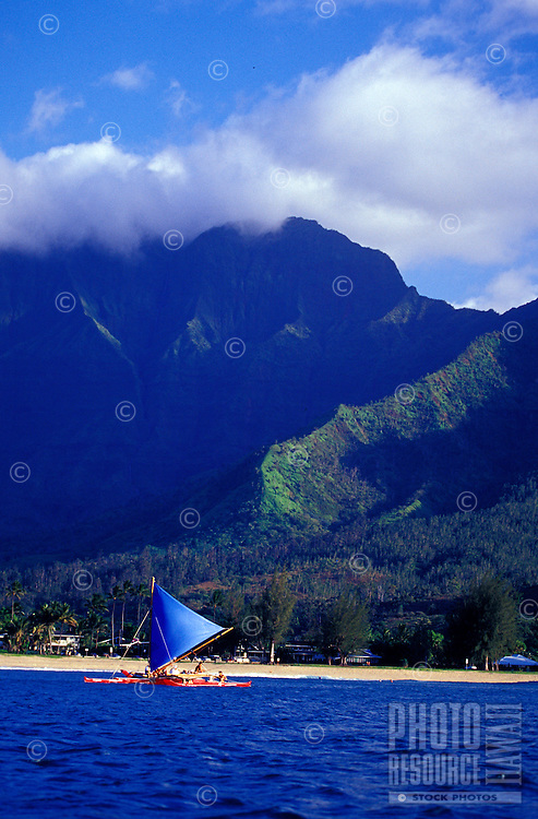 Hawaiian outrigger sailing canoe in tradewinds with Mount Waialeale in background, on Hanalei Bay, Kauai