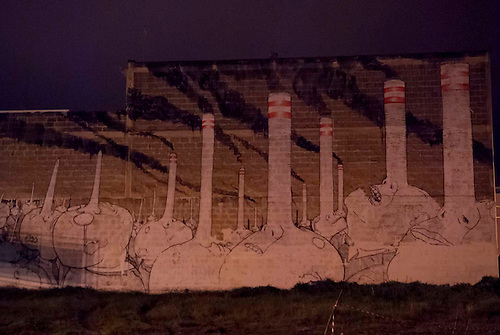 Taranto, Italie, Jan 2010. Une peinture murale represente les nez longs de supposes patrons d'industrie dont les nez sont devenus des cheminees. Tarente est la ville la plus polluée par émissions industrielles en Europe. A Tarente, chacun des 210 000 habitants respire chaque année 2,7 tonnes de monoxyde de carbone et 57,7 tonnes de dioxydes de carbones. Le quartier ouvrier de Tamburi, tout proche de la zone industrielle souffre très directement de la pollution industrielle. Image issue de la Serie La Poussiere Rouge.
