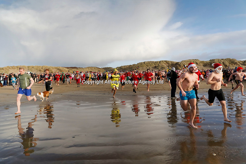 Pictured: People in fancy dress run towards the sea. Tuesday 26 December 2017<br /> Re: Hundreds took part in this year's Boxing Day Walrus Dip which see people in fancy dress taking to the sea at Cefn Sidan beach in Pembrey Country Park, west Wales, UK.