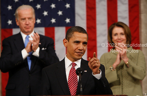 Washington, DC - February 24, 2009 -- United States President Barack Obama gestures during his address to a joint session of Congress in the House Chamber of the Capitol in Washington , Tuesday, Feb. 24, 2009. Vice President Joe Biden and House Speaker Nancy Pelosi of Calif. applaud at rear..Credit: Pablo Martinez Monsivais - Pool via CNP