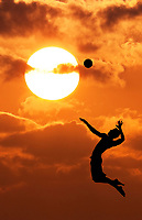 A volleyball player prepares to hit a volleyball, silhouetted against the setting sun, Waikiki, Honolulu, O'ahu.