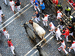 Participants run with Adolfo Martin´s bulls during the seventh bull run in the San Fermin Festival on July 13, 2014, in Pamplona, Basque Country. Every year, tens of thousands of people pack Pamplona's streets for a drunken kick-off to one os worls's best-known fiesta: the nine-day San Fermin bull-running festival. (Ander Gillenea / Bostok Photo)