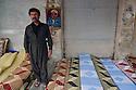 Iraq 2011 <br />  A strret seller with rugs and a portrait of Masoud Barzani on the wall in Erbil  <br /> Irak 2011 <br /> Un vendeur dans une rue d'Erbil avec ses nattes sur le trottoir et le portrait de Masoud Bareani sur le mur