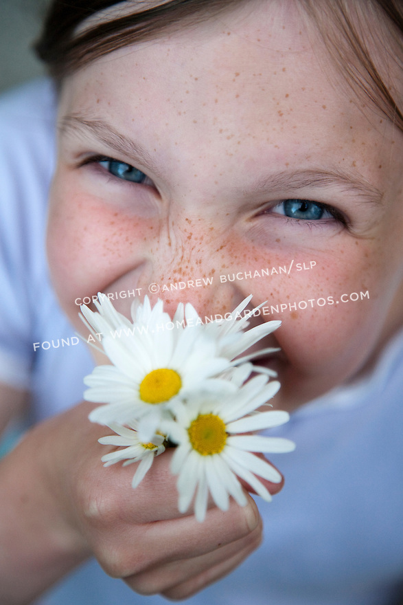 a model-released close up image of a smiling, happy, six-year-old girl's blue eyes and freckled cheeks partially hidden by a small bouquet of yellow and white daisies that she's holding close to her face