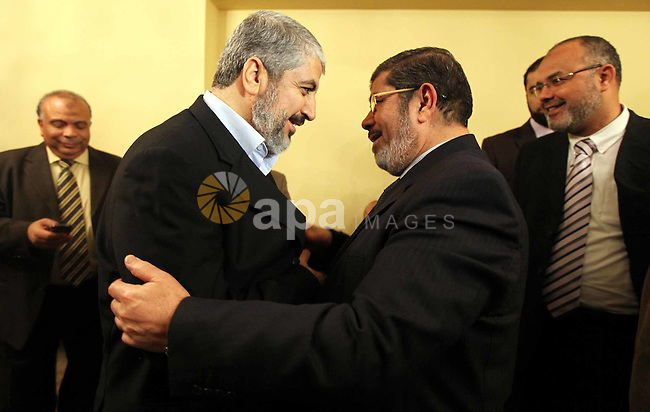 A handout photograph released by the Hamas Press Office shows Leaders of the newly formed Freedom and Justice Party, President Mohammed Morsy, meets with Palestinian Hamas leader Khaled Meshaal (R) in Cairo, Egypt, 21 January 2012. Photo by Mohammed al-Hams