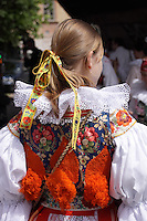 Young woman dressed in the traditional Moravian Costume at the ride of the Kings in Prague May 2015.<br /> <br /> Twelve-year-old Frantisek Libosvar dressed as a girl and with a rose in his mouth leads the royal procession during Ride of the Kings as part of Navalis Celebrations on May 15, 2015 in Prague, Czech Republic. The Navalis Saint John's celebrations take place to commemorate Czech saint and Prague native, Saint John of Nepomuk, patron of all people of the water. <br /> <br /> <br /> The Ride of the Kings takes place during the spring, as a part of the Pentecost traditions . A group of young men ride through a Prague in a ceremonial procession. The ride is headed by chanters, followed by pageboys with unsheathed sabres who guard the King &ndash; a young boy with his face partially covered, holding a rose in his mouth &ndash; and the rest of the royal cavalcade. The King and pageboys are dressed in women&rsquo;s ceremonial costumes, while the other riders are dressed as men. The entourage rides on decorated horses, stopping to chant short rhymes that comment humorously on the character and conduct of spectators. The chanters receive donations for their performance, placed either in a money box or directly into the riders&rsquo; boots. The King&rsquo;s retinue returns home after a few hours of riding, and celebrates in the evening at the house of the King with a small feast, music and dancing. The practices and responsibilities of the Ride of the Kings are transmitted from generation to generation. The traditional paper decorations for the horses and the ceremonial costumes, in particular, are made by women and girls familiar with the processes, colour patterns and shapes specific to each village.