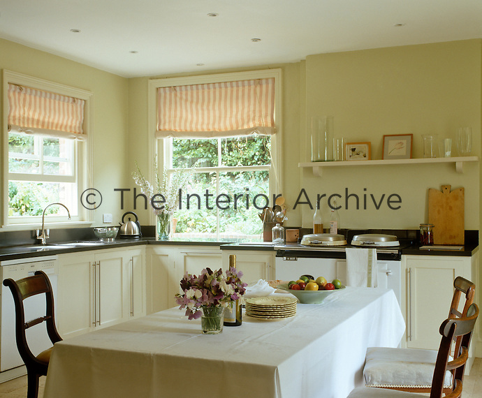 The dining table occupies the centre of this country kitchen furnished with an Aga and contemporary kitchen units