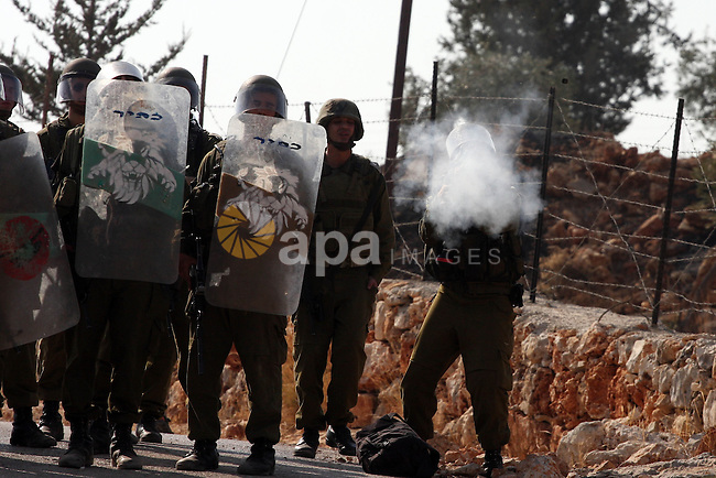Israeli soldiers fire tear gas canisters towards Palestinian and foreign activists during a protest against Israel's separation barrier as masked Palestinian stones throwers clash with Israeli soldiers in the West Bank village of Bilin, near Ramallah, on November 12, 2010. Clashes erupted during the weekly demonstrations, which are aimed at halting the construction of Israel's controversial separation barrier that is mostly built inside the occupied territory and cuts off farmers from their land in border communities like Nilin. Photo by Issam Rimawi