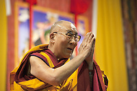 "Switzerland. Basel. St. Jakobshalle. His Holiness the Dalai Lama is greeting the audience at the end of his public lecture on Bodhicitta. He holds his hands kept close to the chest in devotional attitude with the palms and fingers joined as a sign of respect. The gesture is also called the simple namaste (prayer) position (means ""I bow to you.""). The 14th and current Dalai Lama is Tenzin Gyatso, recognized since 1950. He is the current Dalai Lama, as well as the longest-lived incumbent, well known for his lifelong advocacy for Tibetans inside and outside Tibet. Dalai Lamas are amongst the head monks of the Gelug school, the newest of the schools of Tibetan Buddhism. The Dalai Lama, also called "" Ocean of Wisdom"" is considered as the incarnation of Chenresi, the Bodhisattva of compassion who is also the protective deity of Tibet. 7.02.2015 © 2015 Didier Ruef"