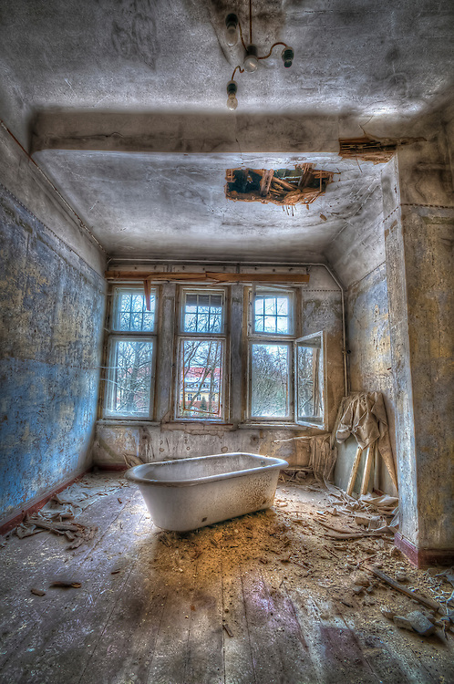 Derelict asylum interior with bath
