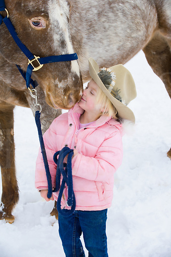 Little blonde girl kissing big Appaloosa horse outdoors in snow, close up of preschooler wearing pink winter coat and cowby hat with animal, Pennsylvania, PA, USA.