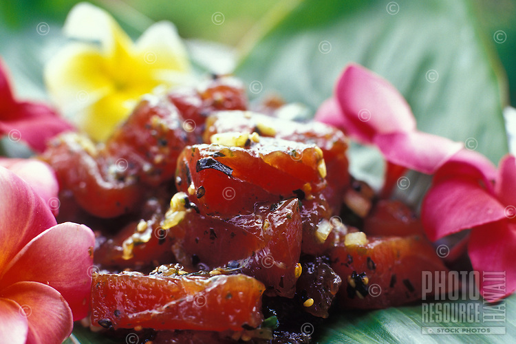 """Closeup of """"""""poke"""""""", a local favorite made with raw tuna, on a banana leaf with plumeria blossoms."""