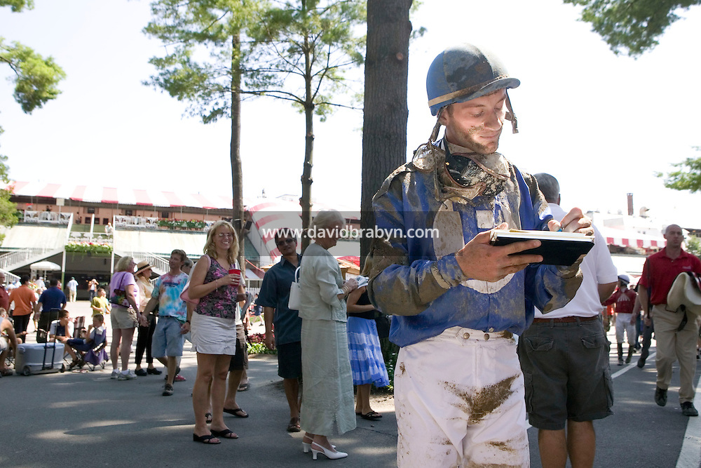 Jockey Julien Leparoux (R, foreground) signs an autograph for a fan (not pictured) after a race in Saratoga Springs, NY, United States, 4 August 2006.