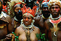 Bare-breasted tribeswoman and tribesmen wearing face paints, bone necklaces and feathered headdress during  a gathering of tribes at Mount Hagen in Papua New Guinea