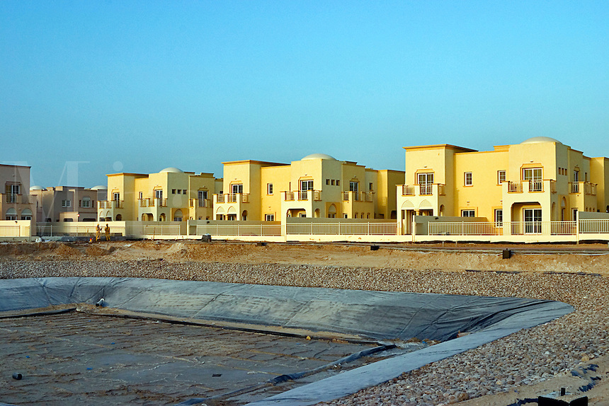 Dubai, United Arab Emirates. New private housing estate under construction, landscaping and artificial lake..