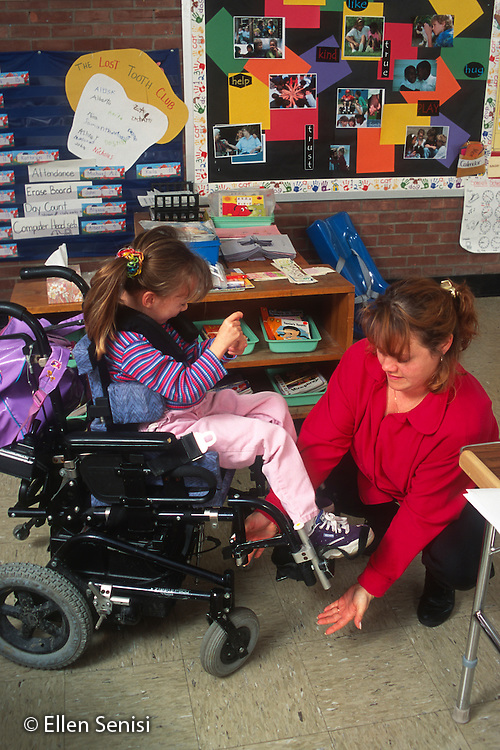 MR / Zoller Public Elementary School. Grade 1 Inclusion Class. Aide helps girl (6, cerebral palsy) get in wheelchair. MR: Gui3, Her4. © Ellen B. Senisi