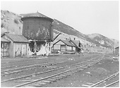 A southeast-facing view of the RGS Rico yards showing the section car shed, water tank, and depot.  There is residual ice and snow under the tank suggesting early spring.<br /> RGS  Rico, CO  Taken by Chione, A. G. - 1952
