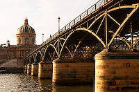 The bridge Pont des Arts in Paris (France) over the Seine river leading to the Academie Francaise (Institut de France) with a man standing on the bridge smoking. Paris France Europe