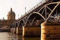The bridge Pont des Arts in Paris (France) over the Seine river leading to the Academie Francaise (Institut de France) with a man standing on the bridge smoking. Paris France Europe