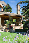 a covered porch and patio on the end of this large, lodge like estate sized home boasts outdoor seating and dining and a large masonry fireplace and chimney to make great outdoor living space under a sunny blue sky.  Design by Sander Groves Landscapes, Inc.