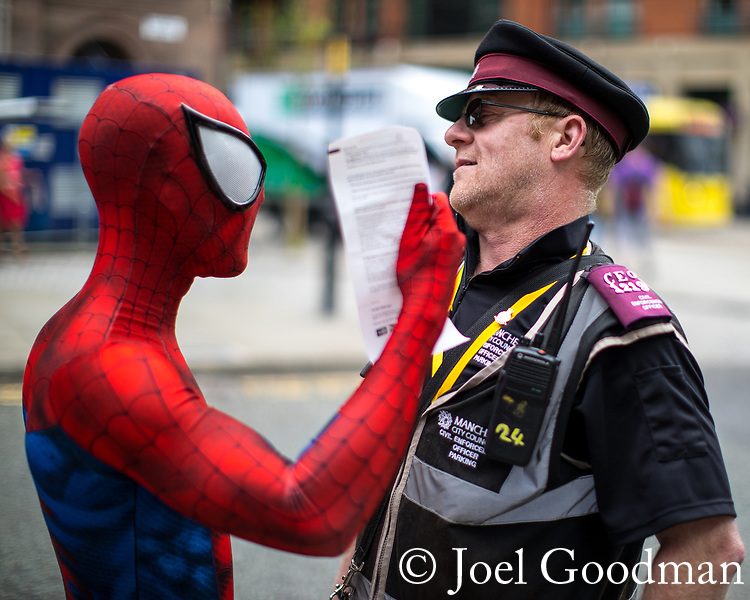 © Joel Goodman - 07973 332324. 30/07/2017 . Manchester , UK . Spiderman argues about a ticket with a parking warden . Cosplayers, families and guests at Comic Con at the Manchester Central Convention Centre . Photo credit : Joel Goodman
