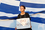 Supporters of the NO vote in the upcoming referendum hold a banner with colors of the Greek flag reading ''NO, OXI'' during a rally at Syntagma. Anxious Greek pensioners swarmed closed bank branches and long lines snaked outside ATMs as Greeks endured the first day of serious controls on their daily economic lives ahead of a July 5 referendum that could determine whether the country has to ditch the euro currency and return to the drachma.