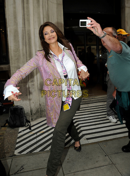 LYNDA CARTER.Leaving BBC Radio 2, London, England..September 14th, 2010.linda full length purple pink white jacket shirt grey gray trousers posing fan smiling camera taking picture leaning bending photograph funny tie.CAP/IA.©Ian Allis/Capital Pictures.