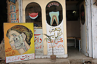 Some rather gruesome illustratios draw attention to a  dentist's surgery in the Old City of Lahore.