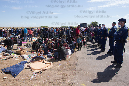 Line of police officers stands guard at a collection point of illegal migrants near Roszke (about 174 km South of capital city Budapest), Hungary on September 07, 2015. ATTILA VOLGYI