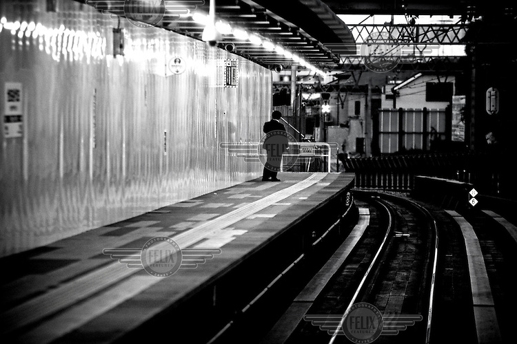 A lone businessman stands on a platform at a train track in Tokyo. According to a government survey in 2005, 23.4% of male workers in their 30s work more than 60 hours a week.