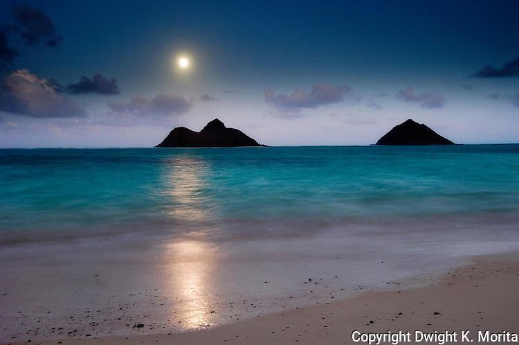 Full moon rising over Mokulua Islands in Lanikai during the twilight just after sunset.