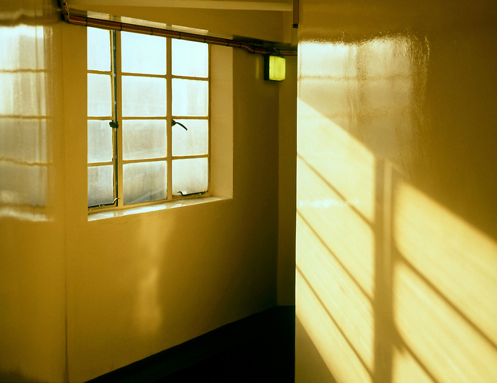 Sunlight pours through a dirty window into the corridor of a block of flats in Clapham, London. England 1989.