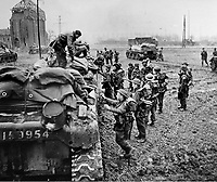 BNPS.co.uk (01202 558833)<br /> NARA/BNPS<br /> <br /> British infantrymen climb aboard a 79th Armoured Division an allied tank as they fought to cross the Rhine. <br /> <br /> Remarkable rarely seen photos of heroic Allied soldiers fighting their way across Europe before crossing the River Rhine 75 years ago feature in a new book.<br /> <br /> They are published in Images of War, Montgomery's Rhine Crossing, which tells the story of the legendary offensive, nicknamed Operation Plunder, in March 1945.<br /> <br /> On the night of March 23, Field Marshal Bernard Montgomery's 21st Army Group launched a massive artillery, amphibious and airborne assault to breach the historic defensive water barrier protecting northern Germany.<br /> <br /> At the same time, the Americans, with the support of the British 6th Airborne Division, set in motion Operation Varsity - involving 16,000 paratroopers - on the east bank of the Rhine. They were dropped here to seize bridges to prevent German reinforcements from contesting the bridgeheads.<br /> <br /> Fierce fighting ensued, with much bloodshed on both sides as the Allies met determined resistance from machine gun nests. But the daring operation proved successful, helping to considerably shorten the war - the Nazis surrendered just six weeks later.