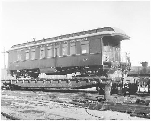 Business car B-7.  Built by D&amp;RG in 1880 as baggage car #17.  Rebuilt in 1886 as business car R.  Renumbered as B-7 in August 1913.  B-7 is on flat car D&amp;RGW 23083 (Standard Gauge).<br /> D&amp;RGW