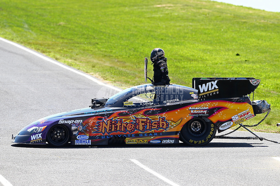 Jun. 1, 2013; Englishtown, NJ, USA: NHRA funny car driver Tony Pedregon climbs from the roof hatch on his car during qualifying for the Summer Nationals at Raceway Park. Mandatory Credit: Mark J. Rebilas-