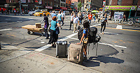 A traveler laden with her luggage waits for a cab in the Chelsea neighborhood of New York on Thursday, June 20, 2013. (© Richard B. Levine)