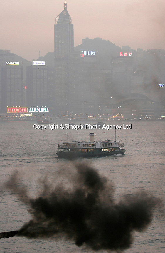 Heavy black smoke emitted from a crane engine on a container barge that pollutes the Victoria harbour in  Hong Kong, SAR, China..02 Dec 2005