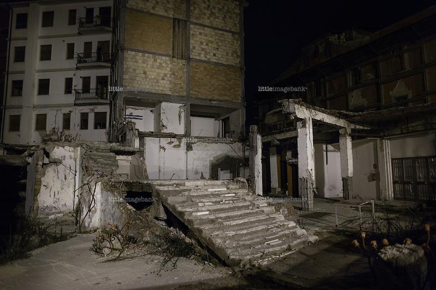 L'aquila, Abruzzo, Italia. 26.03.2014. Byen ligger mørklagt fra solen tar kvelden, og stemningen beskrives av besøkende som noe som minner om en krigssone. En følelse som ikke svekkes av at millitæret kjører rundt i gatene. L'aquila, 6. april 2009 kl. 03:32: Et jordskjelv som måler 6.3 ryster byen. 309 mennesker mister livet. Fem år senere sliter de som overlevde fortsatt med etterskjelvene, i form av en guffen cocktail av uærlige offentlige tjenestemenn, mafia og 494 millioner øremerkede euro på avveie. Fotografier til bruk i feature i DN lørdag 05.04.2014. Foto: Christopher Olssøn.