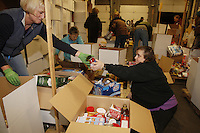 "Friday, February 15, 2013.   Volunteers Lucinda Knopp (R) and Linda Peterson pack an assortment of ""people food"" to be sent out to the 22 checkpoints along the Iditarod trail at Airland Transport in Anchorage."