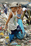 Children working in the municipal dump in Manila, the capital of the Philippines. Children and their parents work day and night in the dump, scavenging for items of value, including plastic, glass and metal, that can be recycled...