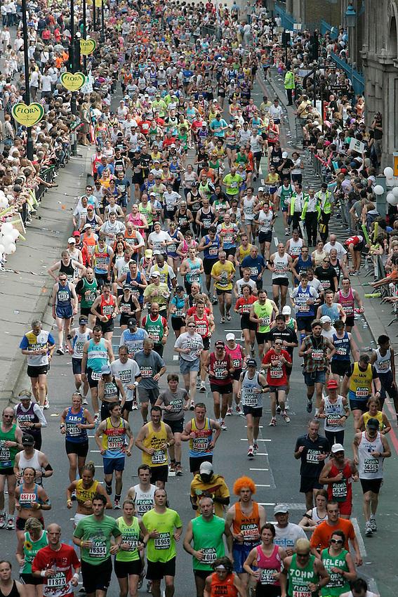 Marathon participants make their way along Lower Thames Street during the 2007 London Marathon.