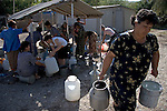 The water is turned on at a series of communal pumps for only 20 minutes each day in the Chalabixan camp for internally displaced people from Nagorno-Karabakh, located near Sheki, Azerbaijan.  Each day, women gather with jugs and buckets to collect the water they'll need for the next 24 hours.
