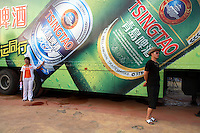 Visitors stand next to a large Tsingtao Beer Advert during the Qingdao Beer Festival in Qingdao, China Tsingtao Brewery is China's largest brewery, founded in 1903 by German settlers, it claims about 12% of domestic market share..