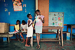 KINSHASA, DEMOCRATIC REPUBLIC OF CONGO - JULY 5: Unidentified girls read and play at a shelter run by Orper, a local NGO on July 5, 2006 in Matonge district in central Kinshasa, Congo, DRC. The NGO has several shelters for homeless boys and girls in Kinshasa and has a program that reunites children with their families. The capital has a growing problem with children displaced by war, poverty and many has been rejected by their families and forced on the streets. About 15,000 children are estimated to live on the streets of Kinshasa. Congo, DRC is in ruins after forty years of mismanagement by the corrupt dictator and former president Mobuto Sese Seko. He fled the country in 1997 and a civil war started. The country is planning to hold general elections by July 2006, the first democratic elections in forty years. (Photo by Per-Anders Pettersson)