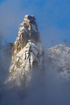 Morning light, fresh snow, and clearing spring clouds on Higher Cathedral Spire, Yosemite Valley, Yosemite National Park, California