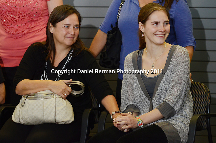 Amanda Knox is comforted by her mother, Edda Mellas, as she acknowledges the handful of supporters cheering her on upon her arrival in the United States at Seattle-Tacoma International Airport in Seattle Tuesday, October 4. Knox's murder conviction was overturned by an Italian appellate court after spending four years in prison in Italy. Photo by Daniel Berman/www.bermanphotos.com