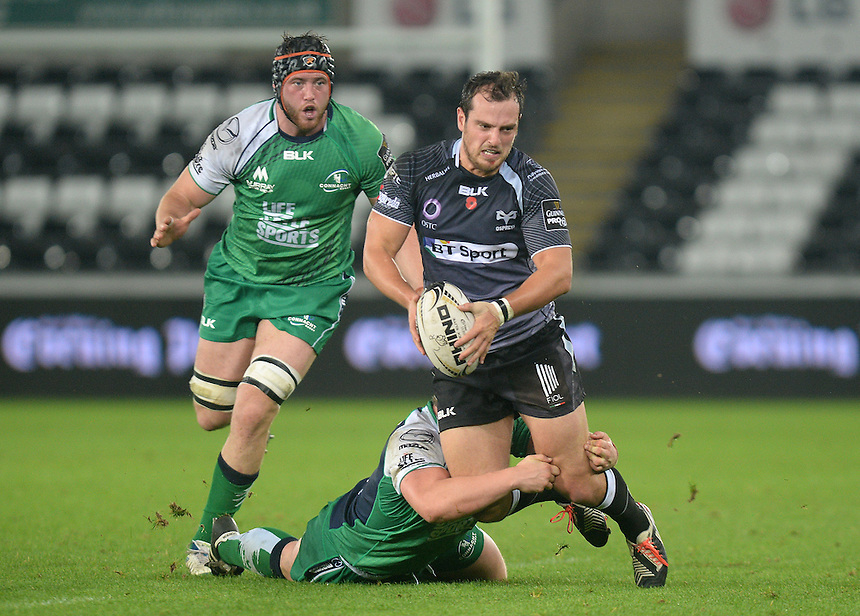 Ospreys's Dan Evans is tackled by Connacht Rugby's Jason Harris-Wright <br /> <br /> Photographer Ian Cook/CameraSport<br /> <br /> Rugby Union - Guinness PRO12 - Ospreys v Connacht Rugby - Friday 31st October 2014 - The Liberty Stadium - Swansea<br /> <br /> &copy; CameraSport - 43 Linden Ave. Countesthorpe. Leicester. England. LE8 5PG - Tel: +44 (0) 116 277 4147 - admin@camerasport.com - www.camerasport.com