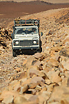 Africa, Mauritania, Sahara Desert, nr. Ouadane (Atar). A Land Rover Defender TD5 Station Wagon ascending on a rough gravel track from the oued Atar-Zouerat onto the ridge of the Guelb er Richat structure. --- Info: The Richat Structure is a prominent circular feature in the Sahara desert of Mauritania near Ouadane. It has attracted attention since the earliest space missions because it forms a conspicuous bull's-eye in the otherwise rather featureless expanse of the desert. The structure, which has a diameter of almost 50 kilometres, has become a landmark for space shuttle crews. Initially interpreted as a meteorite impact structure because of its high degree of circularity, it is now thought to be a symmetrical uplift (circular anticline or dome) that has been laid bare by erosion. Paleozoic quartzites form the resistant beds outlining the structure. The lack of shock metamorphism at the site further backs the latter claim. --- RELEASES AVAILABLE! Automotive trademarks are the property of the trademark holder, authorization may be needed for some uses.